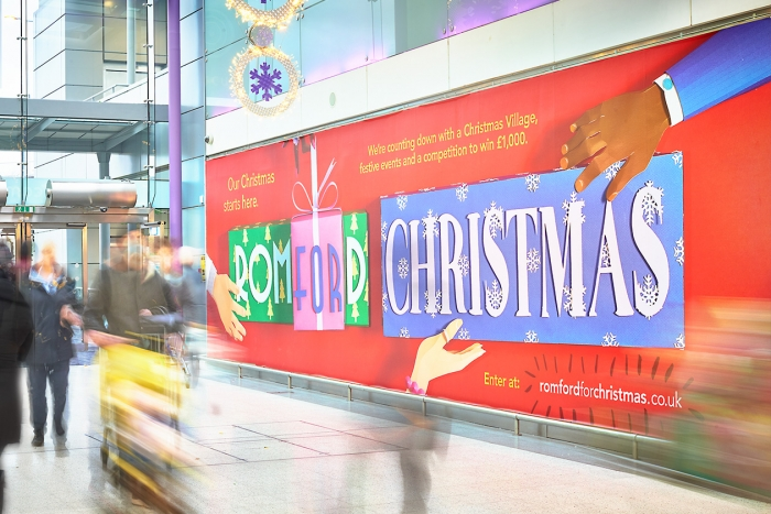 Billboard in shopping centre reading 'Romford For Christmas'.