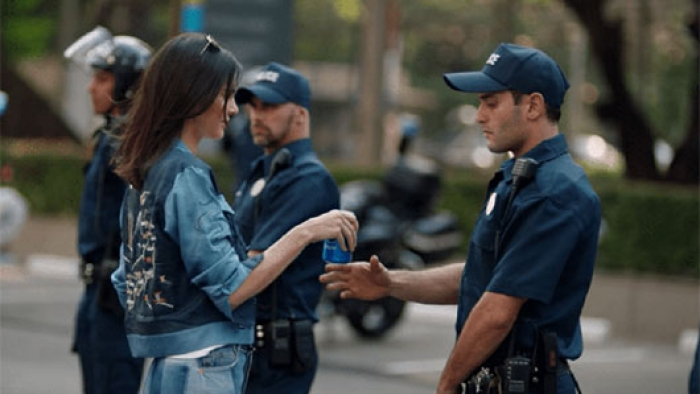 A still from an advert showing Kendall Jenner give a riot policeman a can of Pepsi.