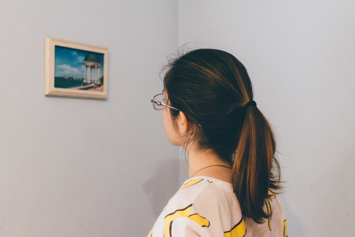 Person looking at art on wall.