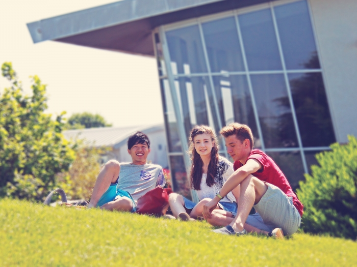 A trio of students sits on the lawn in the sun at Truro and Penwith College.