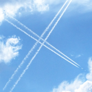 An X formed by the crossing of the cloud-like trails of two aeroplanes.
