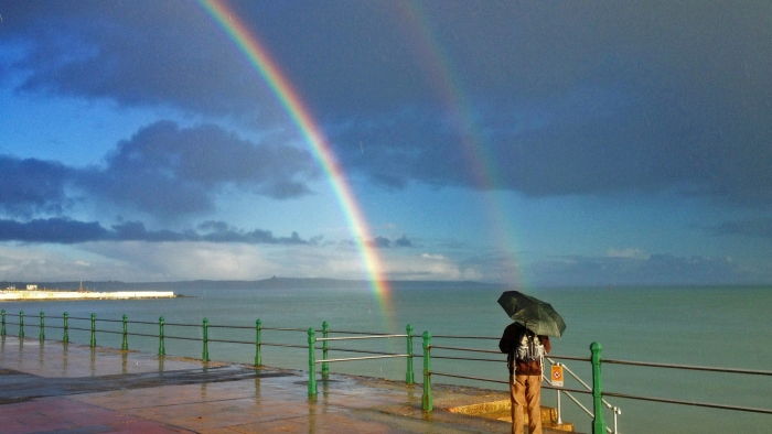 A man stands on Penzance promenade with an umbrella looking at a double rainbow.