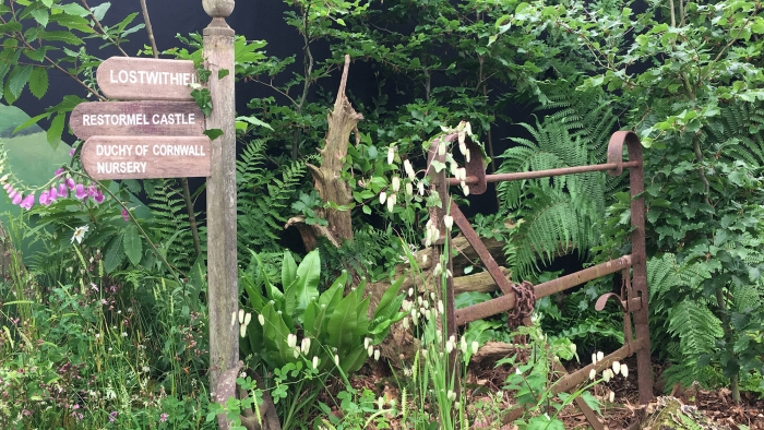 A rusty gate, wooden sign and overgrown path as part of the Duchy of Cornwall Nursery's display at Royal Cornwall Show 2018.