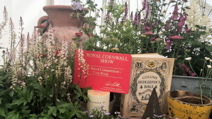 The Royal Cornwall Show stand competition first prize award, placed among flowers at the Duchy of Cornwall stand.
