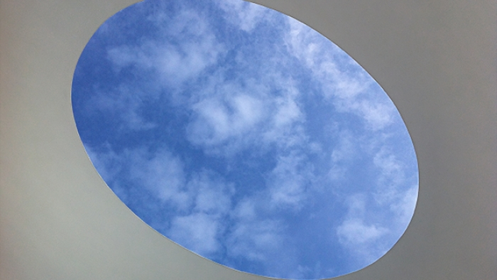 The sky through the open roof of an art installation.