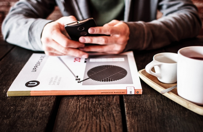 A man looking at a mobile phone with a magazine and coffee on a table.